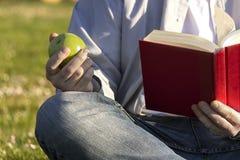 Σπουδαστής που τρώει το λευκό μήλων που διαβάζει ένα βιβλίο Στοκ Φωτογραφία