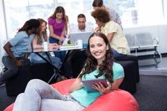 Σπουδαστής που χρησιμοποιεί την ψηφιακή ταμπλέτα με τους φίλους στο υπόβαθρο στοκ εικόνες