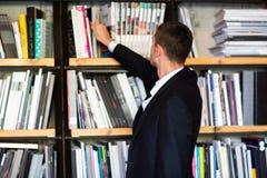 Σπουδαστής σε μια βιβλιοθήκη που επιλέγει ένα βιβλίο ο νεαρός άνδρας επιλέγει ένα βιβλίο στη βιβλιοθήκη Στοκ Φωτογραφία