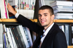 Σπουδαστής σε μια βιβλιοθήκη που επιλέγει ένα βιβλίο ο νεαρός άνδρας επιλέγει ένα βιβλίο στη βιβλιοθήκη Στοκ φωτογραφία με δικαίωμα ελεύθερης χρήσης