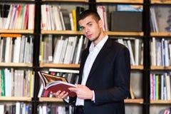 Σπουδαστής στη βιβλιοθήκη Όμορφα βιβλία εκμετάλλευσης νεαρών άνδρων και χαμόγελο στεμένος στη βιβλιοθήκη Στοκ Φωτογραφίες