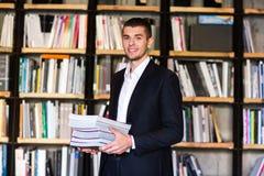 Σπουδαστής στη βιβλιοθήκη Όμορφα βιβλία εκμετάλλευσης νεαρών άνδρων και χαμόγελο στεμένος στη βιβλιοθήκη Στοκ Εικόνες