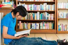 Σπουδαστής στο βιβλίο ανάγνωσης βιβλιοθηκών Στοκ φωτογραφία με δικαίωμα ελεύθερης χρήσης