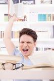 0 σπουδαστής την έκφραση που περιβάλλεται με από τα βιβλία που ρίχνουν ένα BO Στοκ φωτογραφία με δικαίωμα ελεύθερης χρήσης