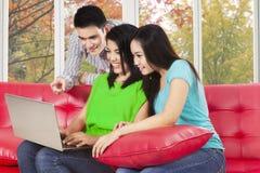 Σπουδαστής τρία που εξετάζει το φορητό προσωπικό υπολογιστή Στοκ Εικόνες