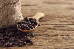 Σπόροι καφέ στο σάκο και το κουτάλι στο τοπ ξύλινο πίνακα Στοκ Εικόνα