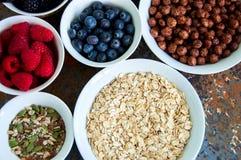 Σπόροι μούρων βρωμών superfood στα κύπελλα σε ένα σκουριασμένο υπόβαθρο Στοκ Εικόνα