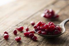 Σπόροι ροδιών στο κουτάλι στο αγροτικό ξύλινο υπόβαθρο Detox, διατροφή, συστατικό φρούτων, μαγειρεύοντας υγιές τρόφιμα ή επιδόρπι στοκ εικόνες
