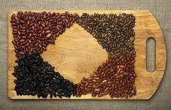 Σπόροι φασολιών που βρίσκονται σε έναν τέμνοντα πίνακα Στοκ Εικόνες