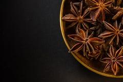 Σπόροι anis μορφής αστεριών στο κύπελλο στη μαύρη πλάκα Στοκ Εικόνες