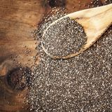 Σπόροι Chia στο ξύλινο κουτάλι στο ξύλινο υπόβαθρο Κύπελλο του σπόρου Chia Στοκ Φωτογραφία