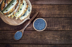 Σπόρος παπαρουνών σε ένα ξύλινο κύπελλο και ένα κουτάλι σε μια καφετιά επιφάνεια Στοκ φωτογραφία με δικαίωμα ελεύθερης χρήσης