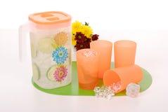 Στάμνα για χυμό και τέσσερα πλαστικά φλυτζάνια Στοκ εικόνες με δικαίωμα ελεύθερης χρήσης