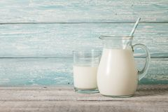 Στάμνα και ποτήρι του γάλακτος στον ξύλινο πίνακα στοκ εικόνες