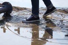 Στάσεις ατόμων με το πόδι του σε μια λακκούβα στοκ εικόνες με δικαίωμα ελεύθερης χρήσης