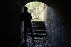 Στάσεις ατόμων στη σκοτεινή σήραγγα πετρών με το καμμένος τέλος Στοκ Εικόνες