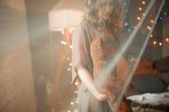 Στάσεις εγκύων γυναικών με τη teddy αρκούδα στο ανοικτό peignoir Άποψη thr Στοκ Εικόνες