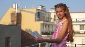 Στάσεις κοριτσιών με έναν χάρτη στο μπαλκόνι απόθεμα βίντεο