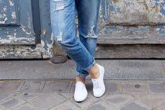 Στάσεις νέων κοριτσιών στα πάνινα παπούτσια crosslegged Στοκ Εικόνες