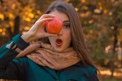 Στάσεις νέων κοριτσιών στο πάρκο και συντηρήσεις Apple κοντά στα μάτια Στοκ φωτογραφία με δικαίωμα ελεύθερης χρήσης