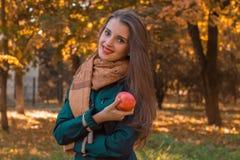 Στάσεις νέων κοριτσιών στο πάρκο που χαμογελά και που κρατά τη Apple Στοκ φωτογραφία με δικαίωμα ελεύθερης χρήσης