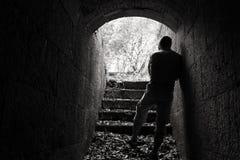 Στάσεις νεαρών άνδρων στη σκοτεινή σήραγγα με το καμμένος τέλος Στοκ Εικόνες