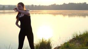 Στάσεις οι έγκυες κοριτσιών σε ένα χαλί, ρίχνουν το βραχίονά της κατά μέρος, στο ηλιοβασίλεμα απόθεμα βίντεο