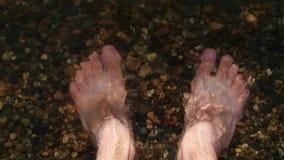 Στάσεις οι ξυπόλυτες ατόμων στο α η ακτή στο νερό, τα πλυσίματα νερού τα πόδια ατόμων, με αντιμετωπίστε σχέδιο φιλμ μικρού μήκους