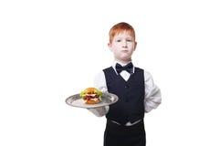 Στάσεις σερβιτόρων μικρών παιδιών με το εξυπηρετώντας χάμπουργκερ δίσκων, που απομονώνεται Στοκ φωτογραφία με δικαίωμα ελεύθερης χρήσης