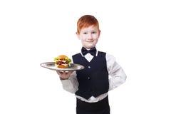 Στάσεις σερβιτόρων μικρών παιδιών με το εξυπηρετώντας χάμπουργκερ δίσκων, που απομονώνεται Στοκ Εικόνες