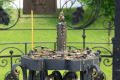 Στάση για τα κεριά εκκλησιών με τα νομίσματα στο νεκροταφείο του ιερού Στοκ Εικόνες