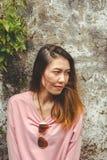 Στάση γυναικών που κλίνει στον παλαιό τοίχο τσιμέντου στοκ εικόνες