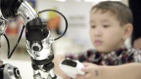 Στάση δύο ασιατική αδελφών αγοριών δίπλα σε ένα ρομπότ και ένα χαμόγελο humanoid η εκμάθηση της πιό πρόσφατης ρομποτικής με τον π φιλμ μικρού μήκους