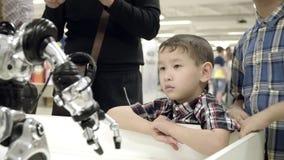Στάση δύο ασιατική αδελφών αγοριών δίπλα σε ένα ρομπότ και ένα χαμόγελο humanoid η εκμάθηση της πιό πρόσφατης ρομποτικής με τον π απόθεμα βίντεο