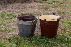 Στάση δύο παλαιά κάδων σιδήρου στο έδαφος Στοκ Φωτογραφία
