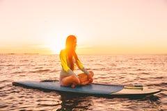Στάση επάνω στο κουπί που επιβιβάζεται σε μια ήρεμη θάλασσα με τα χρώματα ηλιοβασιλέματος Η γυναίκα χαλαρώνει στον πίνακα γουλιάς στοκ φωτογραφίες