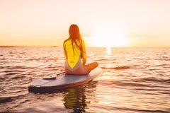 Στάση επάνω στο κουπί που επιβιβάζεται σε μια ήρεμη θάλασσα με τα χρώματα ηλιοβασιλέματος Χαλαρώστε στον ωκεανό στοκ φωτογραφία