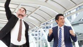 Στάση επιχειρησιακών ατόμων με αίσθημα βέβαιο και επιτυχία που πηδά με τις ευτυχείς συγκινήσεις υπαίθρια απόθεμα βίντεο