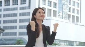 Στάση επιχειρησιακών γυναικών με αίσθημα βέβαιο και επιτυχία με τις ευτυχείς συγκινήσεις υπαίθρια φιλμ μικρού μήκους