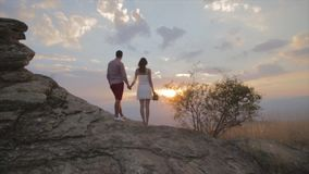 Στάση ζεύγους στο βράχο και ηλιοβασίλεμα προσοχής πάνω από το βουνό απόθεμα βίντεο