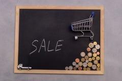 Στάση καροτσακιών αγορών στον πίνακα με τα νομίσματα και την πώληση ` κειμένων ` Στοκ φωτογραφία με δικαίωμα ελεύθερης χρήσης