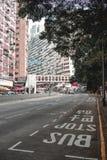 Στάση λεωφορείου σε μια κενή οδό στο Χονγκ Κονγκ με το μεγάλο κατοικημένο κτήριο στο υπόβαθρο στοκ εικόνα με δικαίωμα ελεύθερης χρήσης
