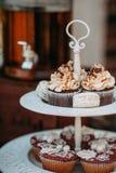 Στάση μετάλλων κάτω από το capcake με την κρέμα, macaroons Στοκ Εικόνες