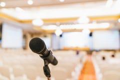 Στάση μικροφώνων θολωμένο στο αίθουσα συνδιαλέξεων υπόβαθρο με το διάστημα αντιγράφων Εκδήλωση δημόσια ανακοίνωσης, συνεδρίαση τη στοκ φωτογραφίες