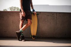Στάση νεαρών άνδρων κλίνοντας στο στηθαίο και κρατώντας ένα longboard Στοκ Φωτογραφίες