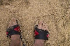 Στάση νεαρών άνδρων που εξετάζει κάτω τα σανδάλια του στην άμμο στοκ φωτογραφίες