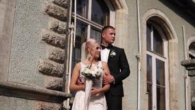 Στάση νεόνυμφων και νυφών στα σκαλοπάτια Πρότυπο μόδας στα κομψά ενδύματα Άσπρο μακρύ φόρεμα και μοντέρνο κοστούμι απόθεμα βίντεο