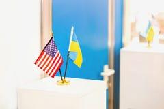 Στάση ουκρανικών και ΑΜΕΡΙΚΑΝΙΚΩΝ σημαιών από κοινού Κλειστή πόρτα στο υπόβαθρο Κυβερνητικές διαπραγματεύσεις Συνεργασία και Στοκ εικόνες με δικαίωμα ελεύθερης χρήσης