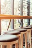 Στάση σκαμνιών φραγμών σε μια σειρά κατά μήκος του παραθύρου σε έναν καφέ Στοκ φωτογραφία με δικαίωμα ελεύθερης χρήσης