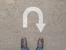 Στάση στο τσιμεντένιο πάτωμα ασφάλτου μπροστά από το σύμβολο στροφής του u Στοκ φωτογραφία με δικαίωμα ελεύθερης χρήσης